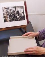 Liliane est non voyante. Elle suit le cours Écouter les photographies. D'abord toucher les quatres bords de la boîte. Ce sont les quatre premières du bord du cadre.