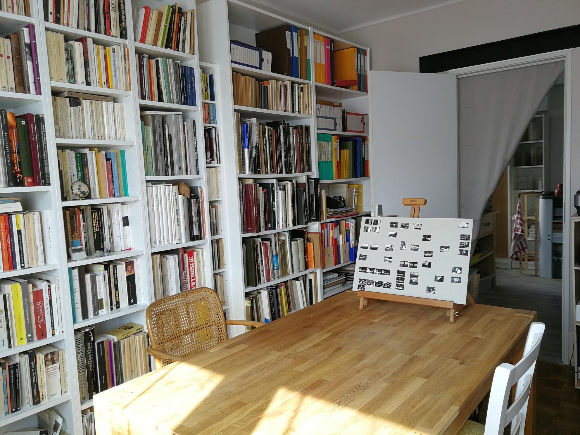 La salle de travail avec sa bibliothèque photo. En fond d'image, le laboratoire pour développer des films et faire des tirages papier.